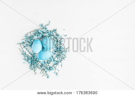 Blue easter eggs and blue flowers on white background. Easter nest. Holiday background. Flat lay top view copy space
