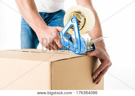 Close-up partial view of young man packing cardboard box