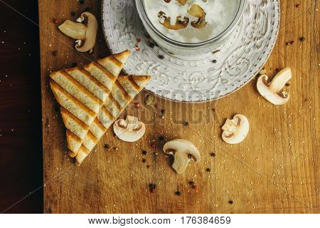 Cream soup with mushrooms champignon in white bowl and circle around plate, bread, vintage style. Top view on desk.