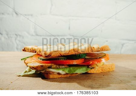 Closeup of ham and vegetables - tomatoes, cucumbers - on whole wheat bread.