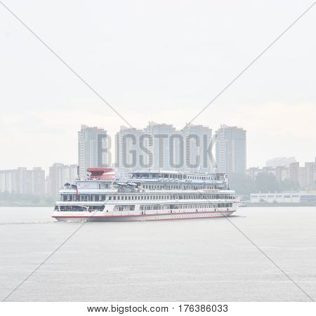 Cruise liner on Neva River on the outskirts of St. Petersburg at cloud day.