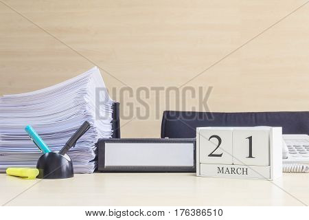 Closeup white wooden calendar with black 21 march word on blurred brown wood desk and wood wall textured background in office room view with copy space selective focus at the calendar