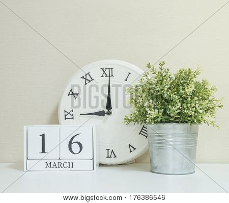 White wooden calendar with black 16 march word with clock and plant on white wood desk and cream wallpaper textured background selective focus at the calendar