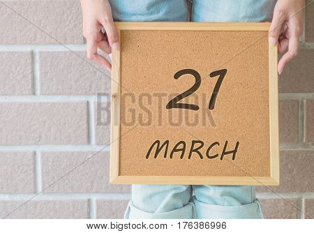 Closeup calendar at the cork board in hand of asian woman in front of her legs with 21 march word on brick wall textured background