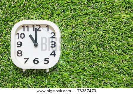 Closeup white clock for decorate in 11 o'clock on green artificial grass floor textured background with copy space