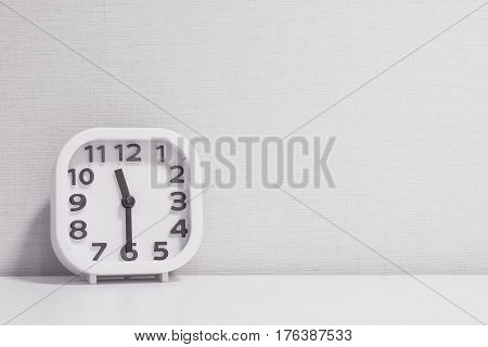 Closeup white clock for decorate show half past eleven or 11:30 a.m. on white wood desk and cream wallpaper textured background in black and white tone with copy space