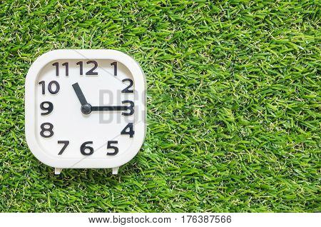 Closeup white clock for decorate show a quarter past eleven o'clock or 11:15 a.m. on green artificial grass floor textured background with copy space