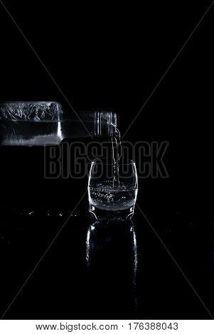 Bottle Vodka Poured Into A Glass On Black Background