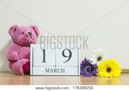 Closeup surface white wooden calendar with black 19 march word on brown wood desk and cream color wallpaper in room textured background with copy space selective focus at the calendar