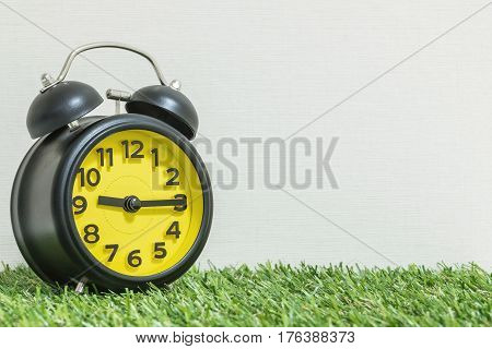 Closeup black and yellow alarm clock for decorate show a quarter past nine o'clock or 9:15 a.m. on green artificial grass floor and cream wallpaper textured background with copy space