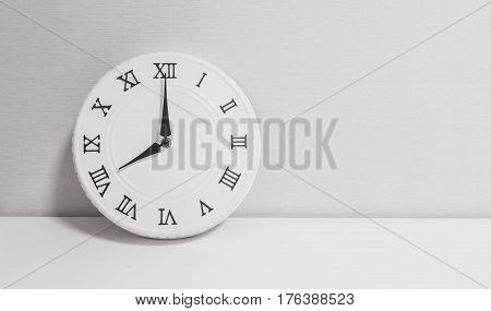 Closeup white clock for decorate in 8 o'clock on white wood desk and wallpaper textured background in black and white tone with copy space