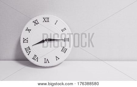 Closeup white clock for decorate show a quarter past eight or 8:15 a.m. on white wood desk and wallpaper textured background in black and white tone with copy space