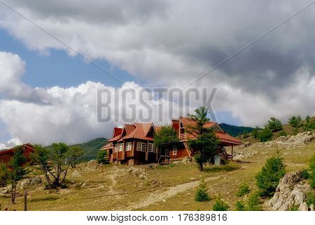 Old Woden house in green mountains and clouds