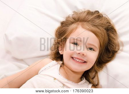 Adorable happy little girl waked up in her bed