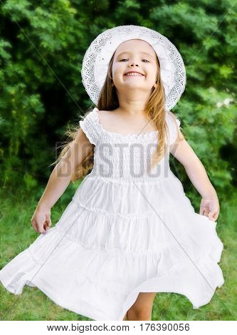 Portrait of adorable happy little girl in white princess dress and hat outdoor