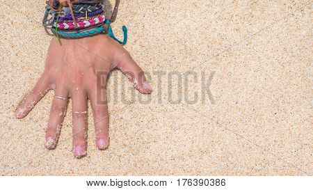 Women Hand with Colourful Wristband Toching Wet Sand on the Beach. Vertical orientated