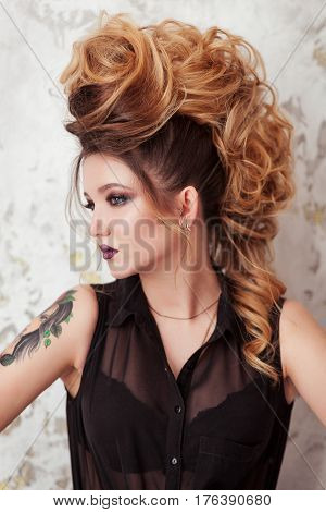 Fashion shiny makeup. Beauty woman with mohawk hairstyle. Blonde sexy model girl with long hair, long eyelashes, perfect skin. Creative unusual mohawk hairstyle. Skincare concept, model head. Rock style.