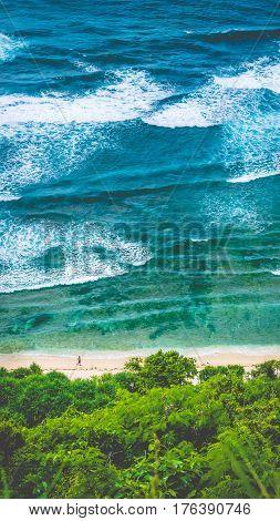 Man walking along of Nunggalan Beach. Big waves rolling on. Uluwatu, Bali, Indonesia.
