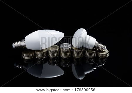 Economy Concept. Modern light emitting diode lamps with coins on black reflective background
