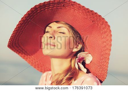 Portrait of a beautiful graceful woman in elegant pink hat with a wide brim. Beauty, fashion concept.