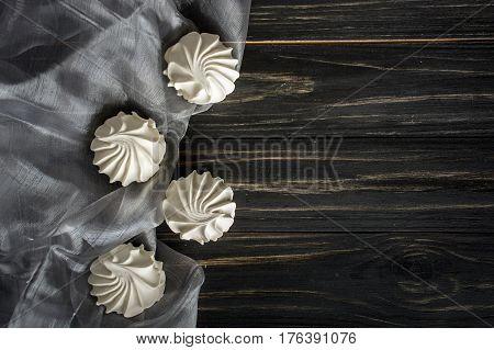 Four white zephyr on dark wooden background