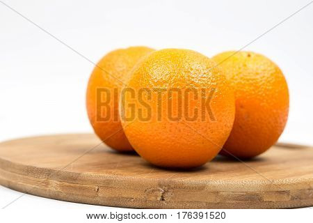 Three Oranges On The Wooden Board With White Background Copy Space