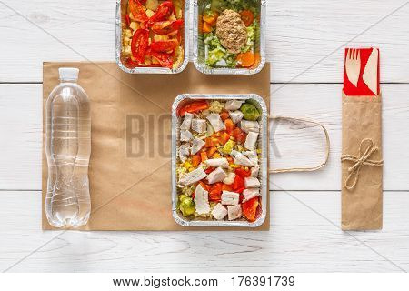 Healthy food, diet takeaway. Daily meals in foil boxes on white wood. Vegetables, salmon, meat and salads. Top view, flat lay