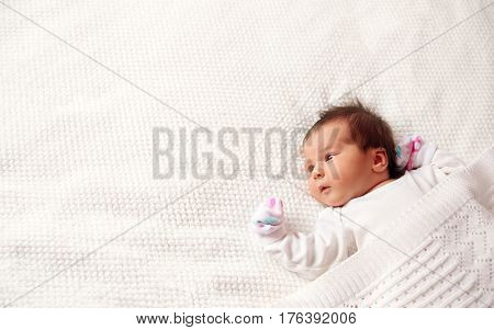 Cute newborn baby girl lying in the bed. Two weeks old infant child on white soft blanket