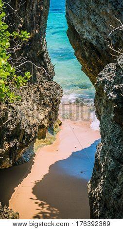 Small hidden Beach between Rockes covered by Cactus on Geger Beach in Nusa Dua Bali.