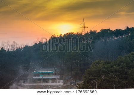 Sun se ting below a tree line with a power line tower and power lines at tree top lever with smoke from a fire rising into the air in front of a house in the foreground