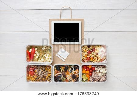 Tablet screen and healthy food delivery, order online concept. Daily meals background. Ready for diet. Vegetables, seafood, meat and fruits in foil box. Top view, flat lay on wood, copy space