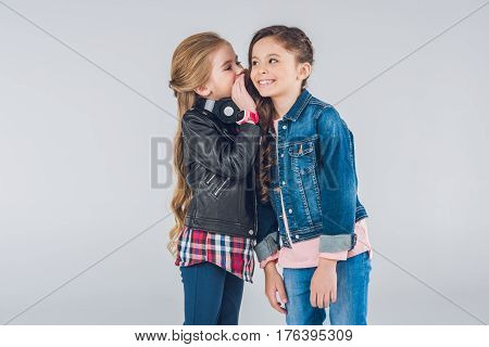 Two Smiling Little Girls Whispering Secrets On Grey