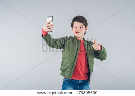 Grimacing Boy Taking Selfie With Smartphone And Showing Thumb Up