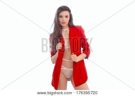 Sexy slim brunette woman posing in studio wearing fashionable jacket and white lacy lingerie. Fashion model in red suit and trendy bra looking at camera against white background