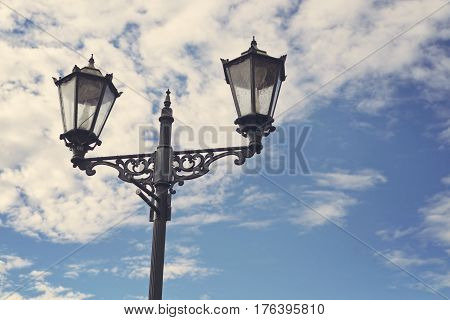 Old classic lamp post and blue sky