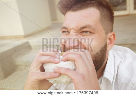 Close-up portrait of insatiable and hungry man eating cheeseburger. Bearded man having a snack during his lunch time. Toned image.
