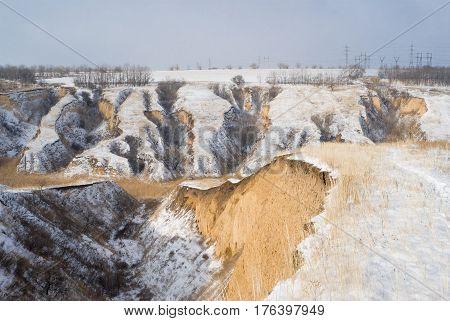 Winter landscape with soil erosion in Ukrainian rural area.