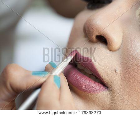 Closeup Of Woman Applying Lipstick