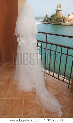 Female bride in lace wedding dress stood on balcony looking to sea of tropical ocean coastal resort