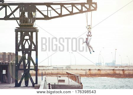 brave man hanging on the crane above the water