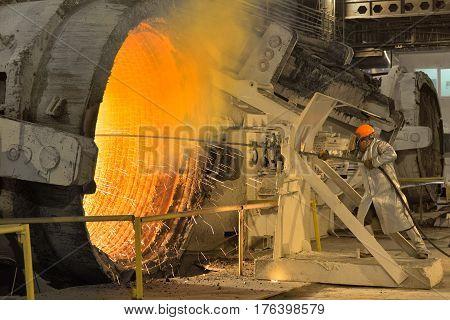 Industrial worker in steel making factory near intense heat
