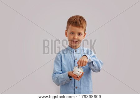 Child's hand put into white piggybank money coins. Making savings concept