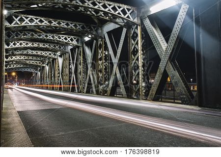 Asphalt Road Under The Steel Construction Of A Bridge In The City. Night Urban Scene With Car Light