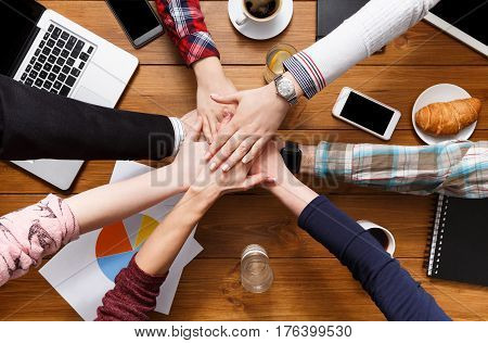 United hands team in office concept. Alliance and cooperation, casual business people connection, top view