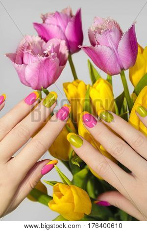Yellow green French manicure with pink nail Polish and tulips closeup. Nail art.