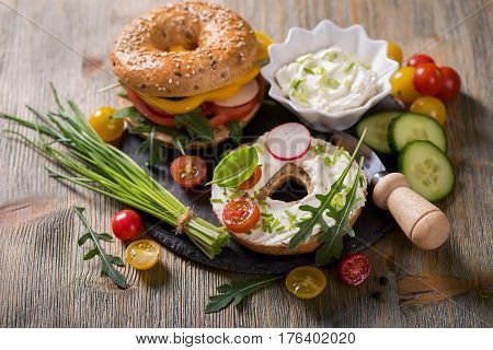 Vegetarian bagel sandwich with fresh veggies cream cheese and arugula salad healthy food lunch breakfast