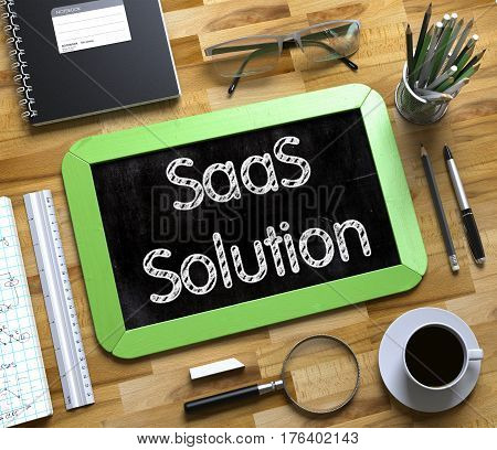 SaaS Solution - Text on Small Chalkboard. Business Concept - SaaS Solution Handwritten on Green Small Chalkboard. Top View Composition with Chalkboard and Office Supplies on Office Desk. 3d Rendering.