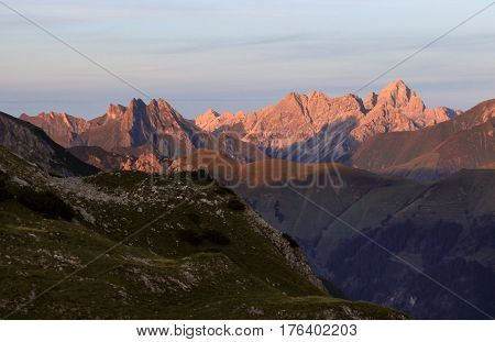 Great clear view from high mountain over other peaks. Evening or morning sunlight illuminates the mountains. Alps, Bavaria, Tirol, Allgau.