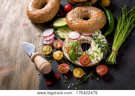 Vegetarian bagel sandwich with fresh veggies cream cheese and arugula healthy food lunch breakfast snack