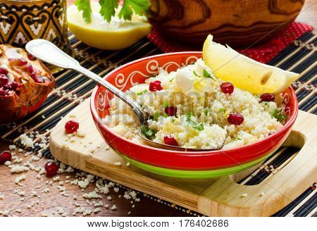 Couscous in oriental style with grains of pomegranate lemon zest and butter selective focus